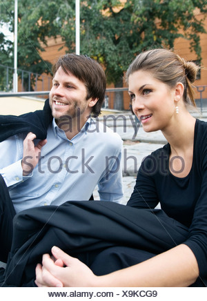 Man and woman sitting on the ground - Stock Photo