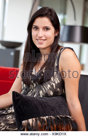 Young woman sitting comfortably on the sofa in her apartment - Stock Photo