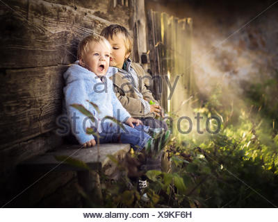 Two brothers sitting on a wall having fun - Stock Photo
