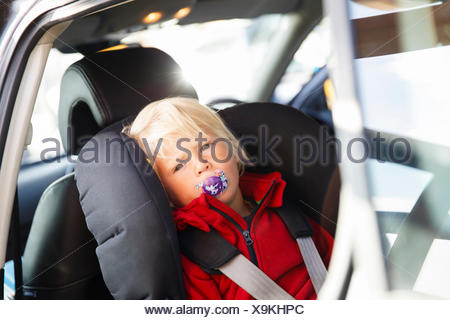 Sweden, Little blonde boy (2-3) fastened to seat in car - Stock Photo