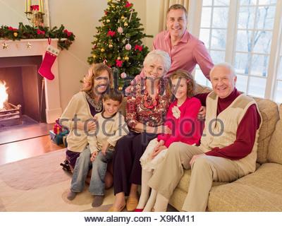 Multi-generation family near Christmas tree in living room - Stock Photo