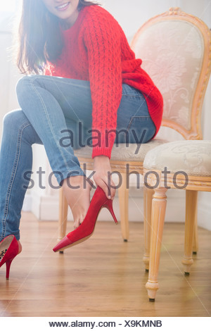 Low section of woman trying on footwear in store - Stock Photo