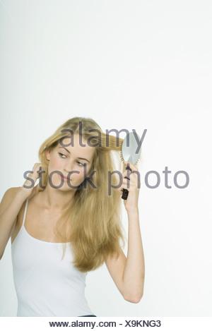 Teenage girl brushing hair - Stock Photo