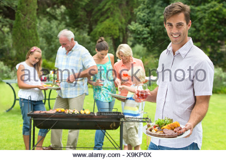 Portrait of smiling man with plate of barbecue and wine glass with family in background - Stock Photo