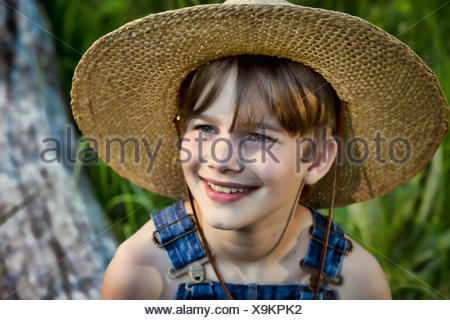 Portrait of a smiling boy wearing a straw hat - Stock Photo