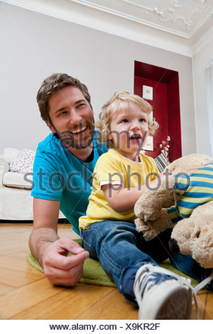 Father and son playing on floor - Stock Photo