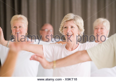 Senior people exercising in an exercise class - Stock Photo