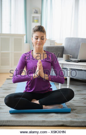 Young woman practicing yoga in living room - Stock Photo