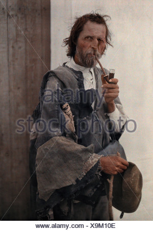 Portrait of a gypsy man smoking a pipe. - Stock Photo