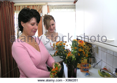 Middle aged mother receiving flower on mothering day from grown up daughter in law - Stock Photo
