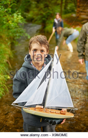 Young boy holding sailing boat in river - Stock Photo