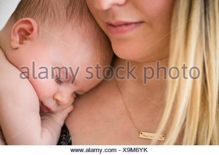 Baby girl (2-5 months) sleeping on mother's shoulder - Stock Photo