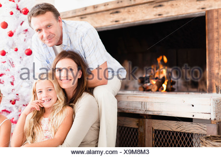 Family relaxing by Christmas tree - Stock Photo