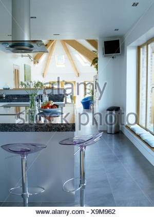 open plan kitchen breakfast bar.  Perspex chrome stools at breakfast bar in modern open plan kitchen Stock Photo Stools and living room