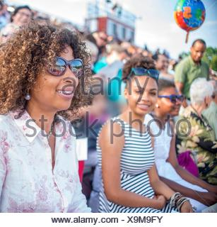 Mature mother and daughters watching graduation ceremony - Stock Photo