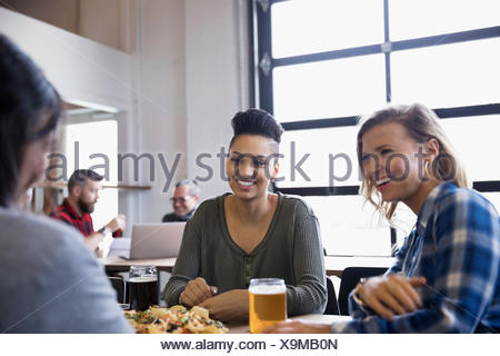 Female friends drinking beer at brewery restaurant table - Stock Photo