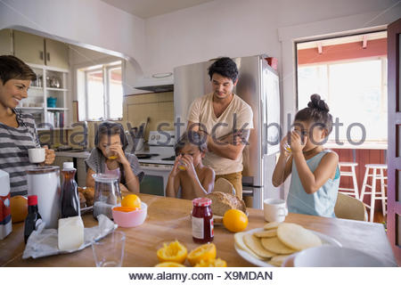 Family enjoying breakfast in kitchen - Stock Photo