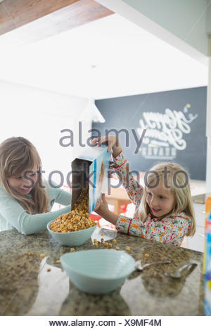 Sisters pouring cereal for breakfast in kitchen - Stock Photo