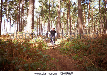 Twin brothers racing BMX bikes in forest - Stock Photo