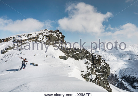 Mid adult male skier walking to top of mountain with skis, Corvatsch, Switzerland - Stock Photo