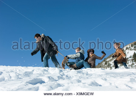 USA, Utah, Big Cottonwood Canyon, family tobogganing in mountains - Stock Photo
