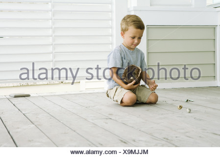 Boy kneeling on the ground, spilling eggs out of bird's nest - Stock Photo