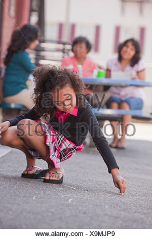 Hispanic girl drawing on the floor with chalk, Boston, Massachusetts, USA - Stock Photo