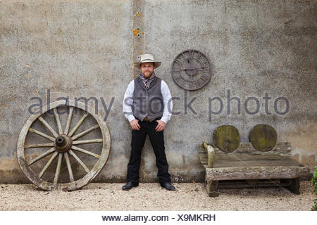 Bearded man wearing Stetson standing with his hands in his pockets outside a barn next to a wooden bench and large wooden carriage wheel. - Stock Photo