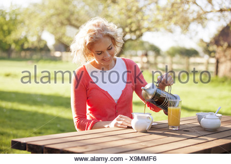 A mature woman sitting at a garden bench pouring coffee - Stock Photo