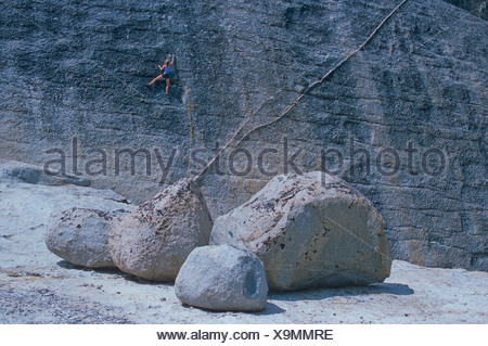 A woman rock climbs in Tuolomne Meadows, Yosemite National Park, CA. - Stock Photo