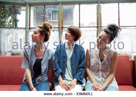 Three women sitting indoors on a bench, looking away. - Stock Photo