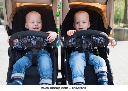 Portrait of baby twin brothers in pushchairs at park - Stock Photo