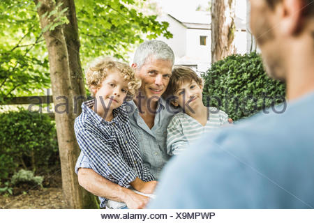 Mid adult man with father and sons in garden - Stock Photo