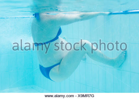 Pregnant woman exercising in swimming pool - Stock Photo
