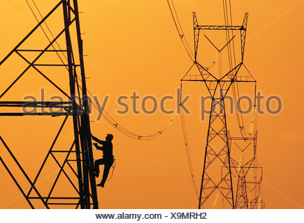A worker climbs an electrical tower, Manitoba, Canada - Stock Photo