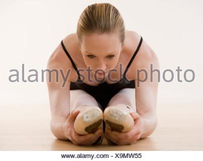 Female ballet dancer stretching on floor - Stock Photo