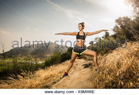 Female runner stretching in rural landscape - Stock Photo