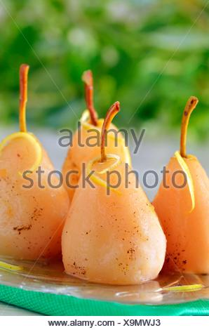 four pears poached in syrup. - Stock Photo