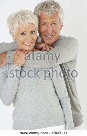 Senior man embracing a senior woman from behind - Stock Photo