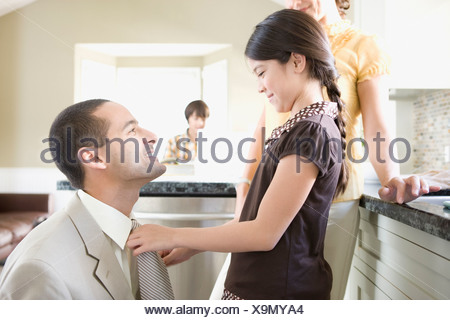 Girl straightening father's tie at home - Stock Photo