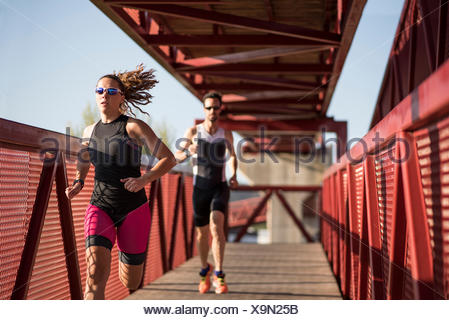 Two athletes running on a bridge - Stock Photo