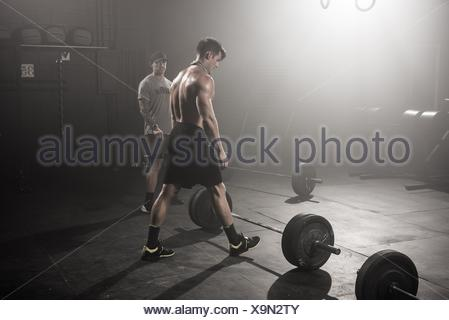 Mid adult man about to lift barbell, while trainer looks on - Stock Photo