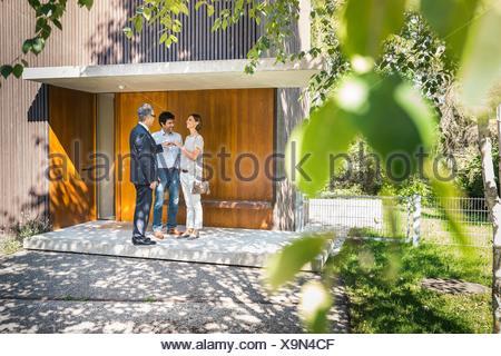 Estate agent handing keys to mature couple outside new house - Stock Photo
