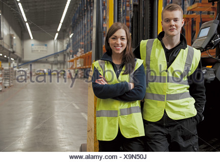 Workers by forklift in warehouse - Stock Photo