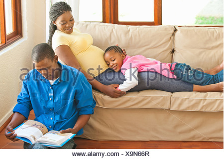 Girl lying on pregnant mothers stomach while her father is reading to them, Johannesburg, Gauteng Province, South Africa - Stock Photo