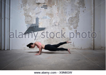 Mid adult woman practicing plank pose in yoga studio, Munich, Bavaria, Germany - Stock Photo