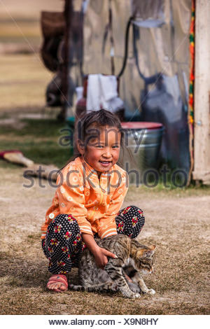 Kyrgyz girl playing with a cat, Kyrgyzstan, Lake Song Kul, Naryn - Stock Photo