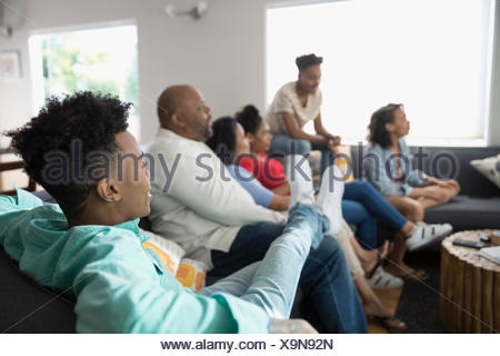 African American family watching TV in living room - Stock Photo