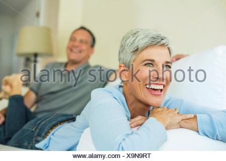 Mature couple laughing and relaxing on sofa - Stock Photo