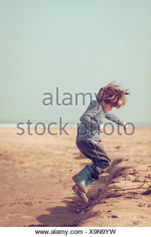 Boy jumping in the sand on the beach, Morocco - Stock Photo